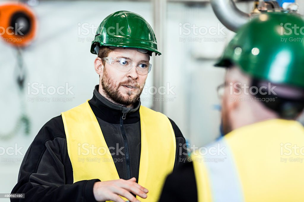 Worker discussing with colleague in factory stock photo