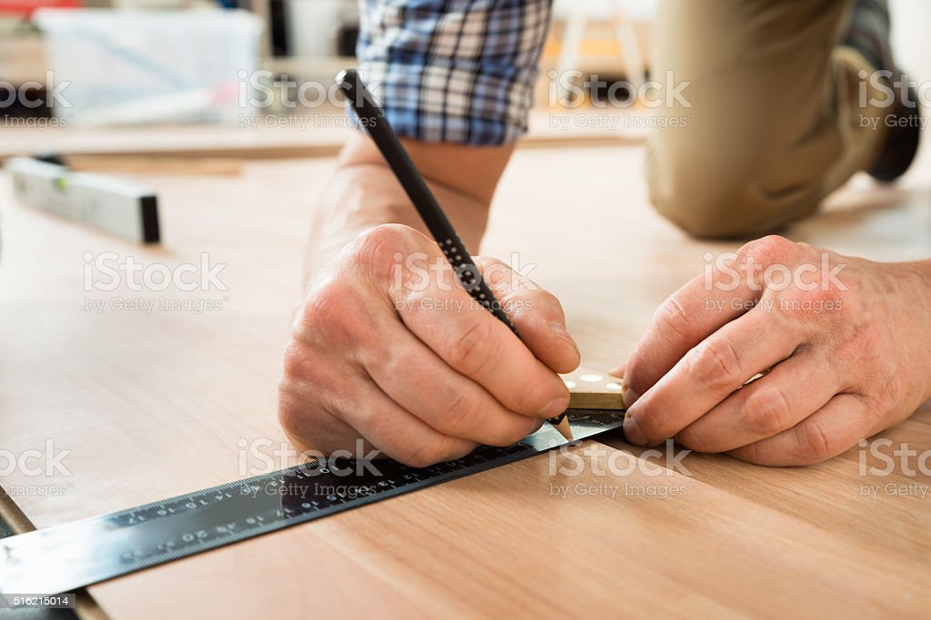 Worker Drawing A Mark On Laminate Using Ruler stock photo