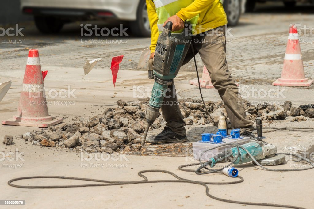 Worker drilling concrete driveway with jackhammer. stock photo