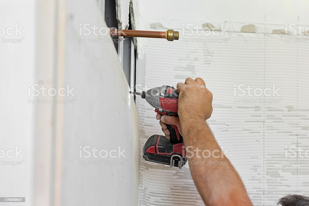 Worker drilling into the wall of an unfinished stall shower royalty-free stock photo