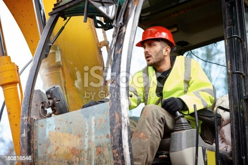 Young male worker driving a excavator at construction site