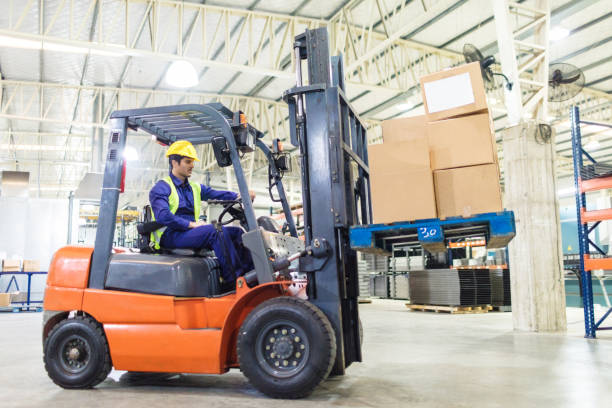 worker driving a forklift in warehouse stock photo