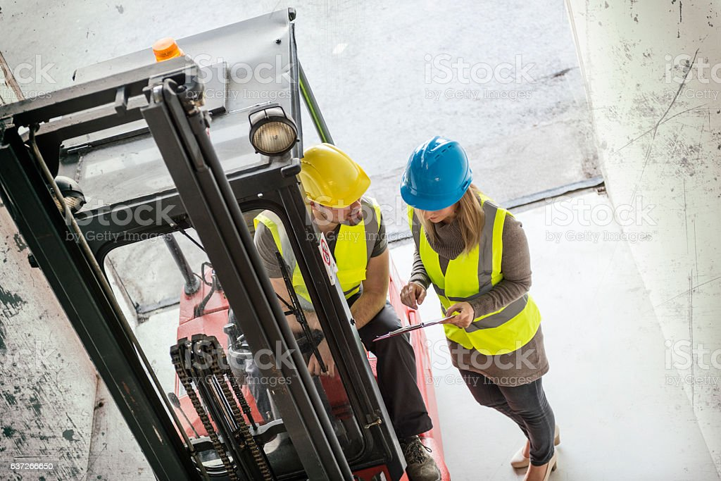 Worker driving forklift discussing with manager in the warehouse stock photo