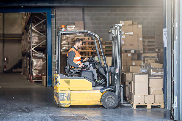 Worker driving forklift in warehouse stock photo