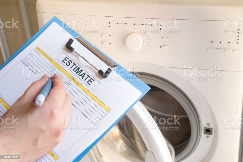 Worker estimating cost for broken washing machine stock photo