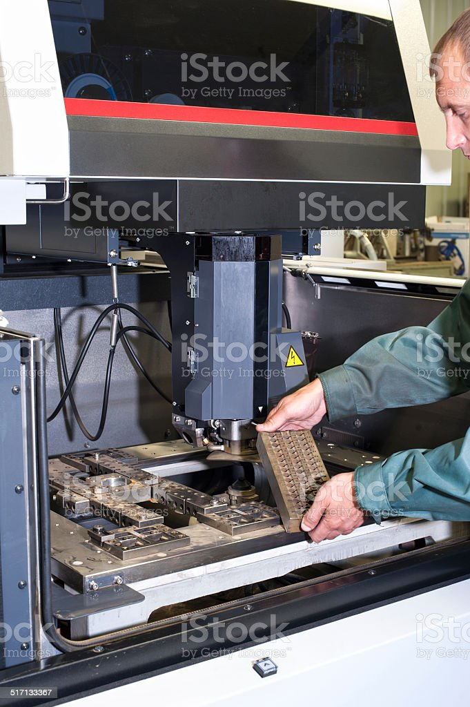 Worker examining metal detail in cnc industrial machine stock photo