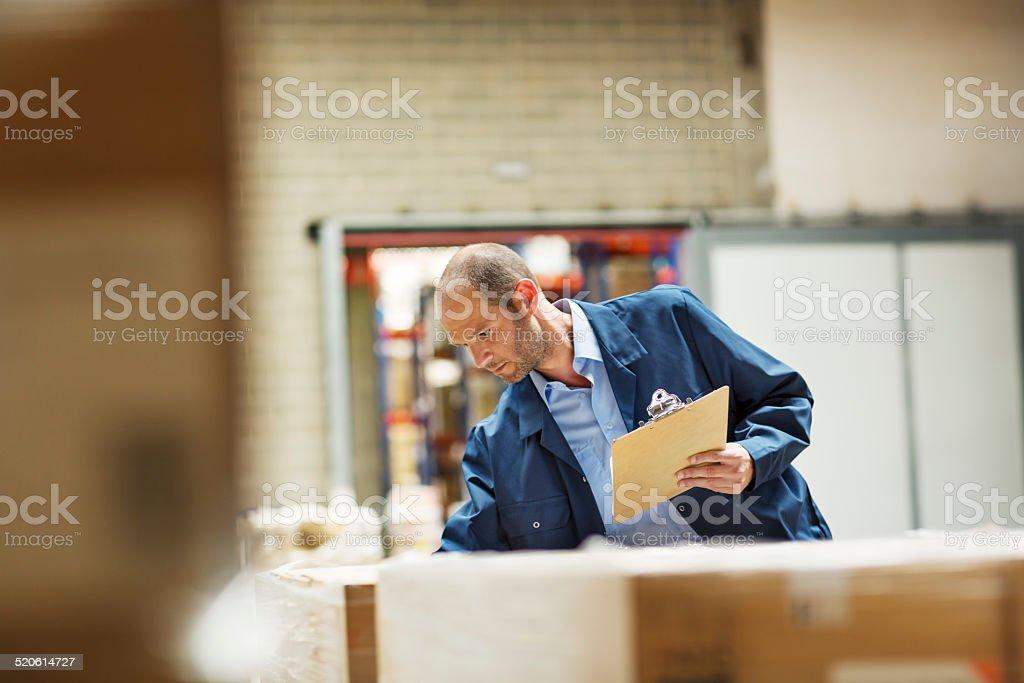Worker examining stock in warehouse stock photo