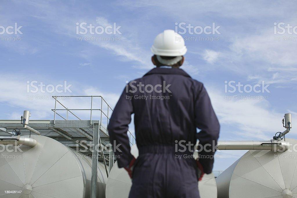 Worker examining tanks outdoors stock photo