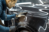 Car service worker examining vehicle body for scratches and damages, taking a car for professional auto detailing. Professional body car inspection concept