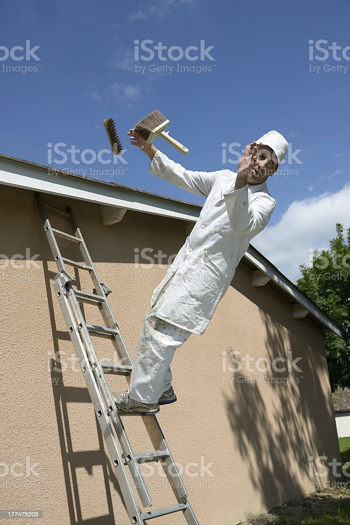 Worker falling off ladder while he was painting stock photo