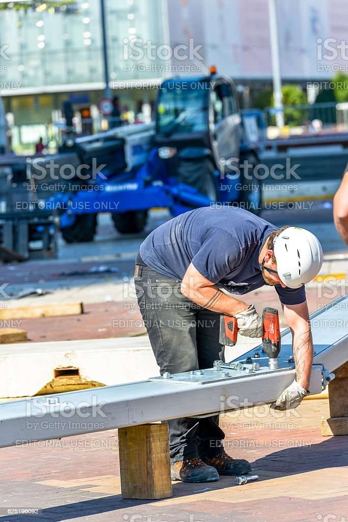 worker fastening a big bolt in a metal beam stock photo
