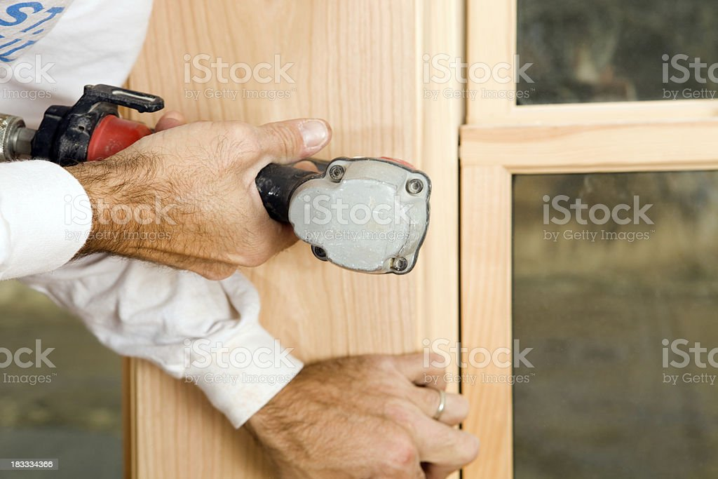 Worker Fastening Window Trim with Pneumatic Nail Gun royalty-free stock photo