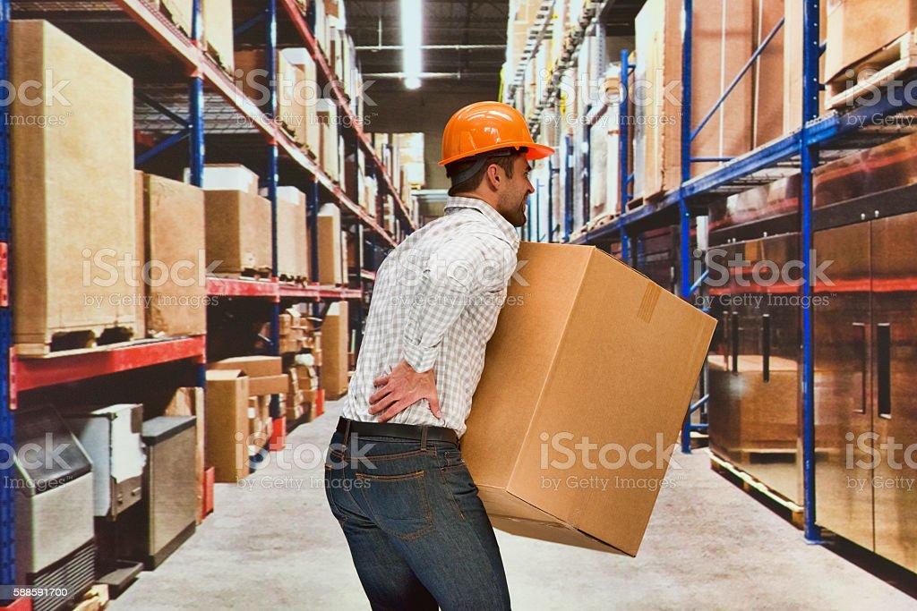 Worker feeling back pain in warehouse stock photo