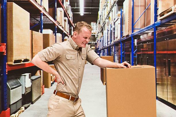 Travailleur sentiment les douleurs du dos dans un entrepôt - Photo