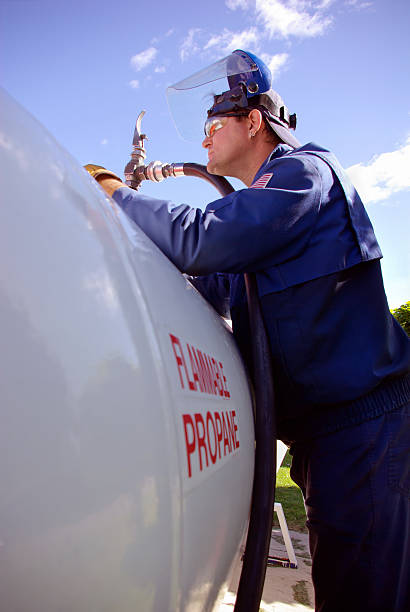 worker filling a large propane tank - mikefahl stock pictures, royalty-free photos & images
