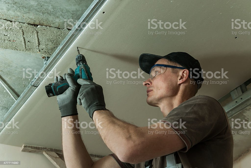 Worker fixes the drywall stock photo