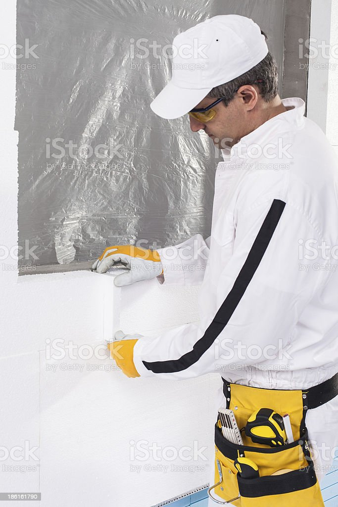 Worker fixing an insulation panel royalty-free stock photo