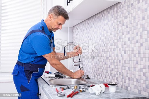 Side View Of A Plumber Fixing Water Tap In Kitchen
