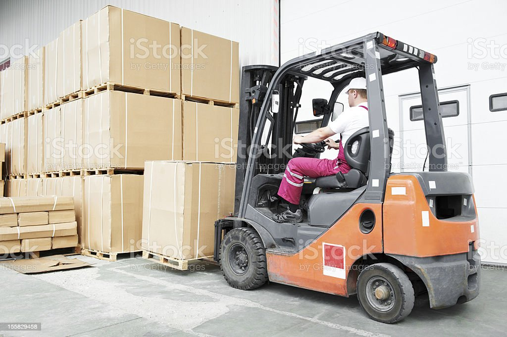 A worker forklift driver at the warehouse royalty-free stock photo