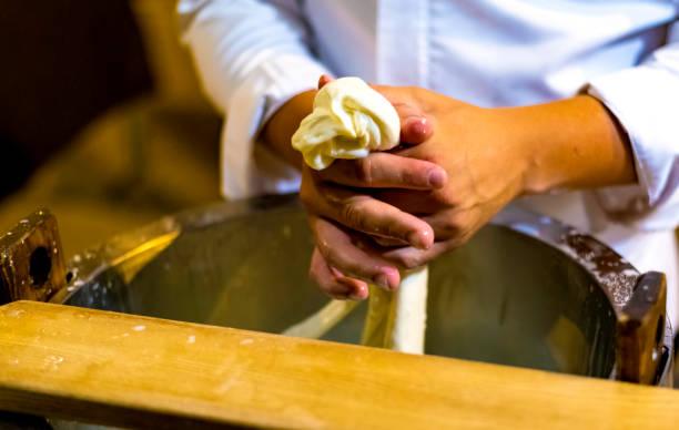 werknemer uit kaasfabriek de productie van mozzarella. selectieve focus - hand constructing industry stockfoto's en -beelden