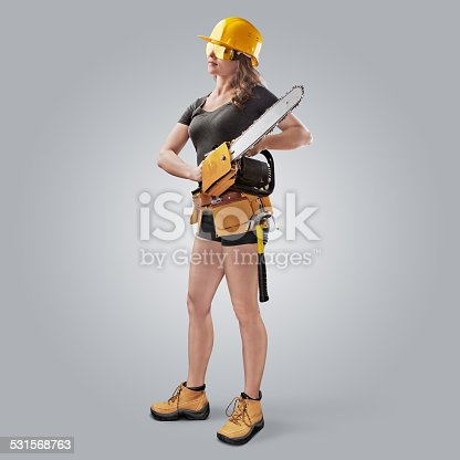 istock worker girl in a helmet with a chain saw 531568763