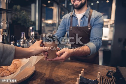 Close up female hand taking cup of hot coffee from barista in confectionary shop. Purchase concept