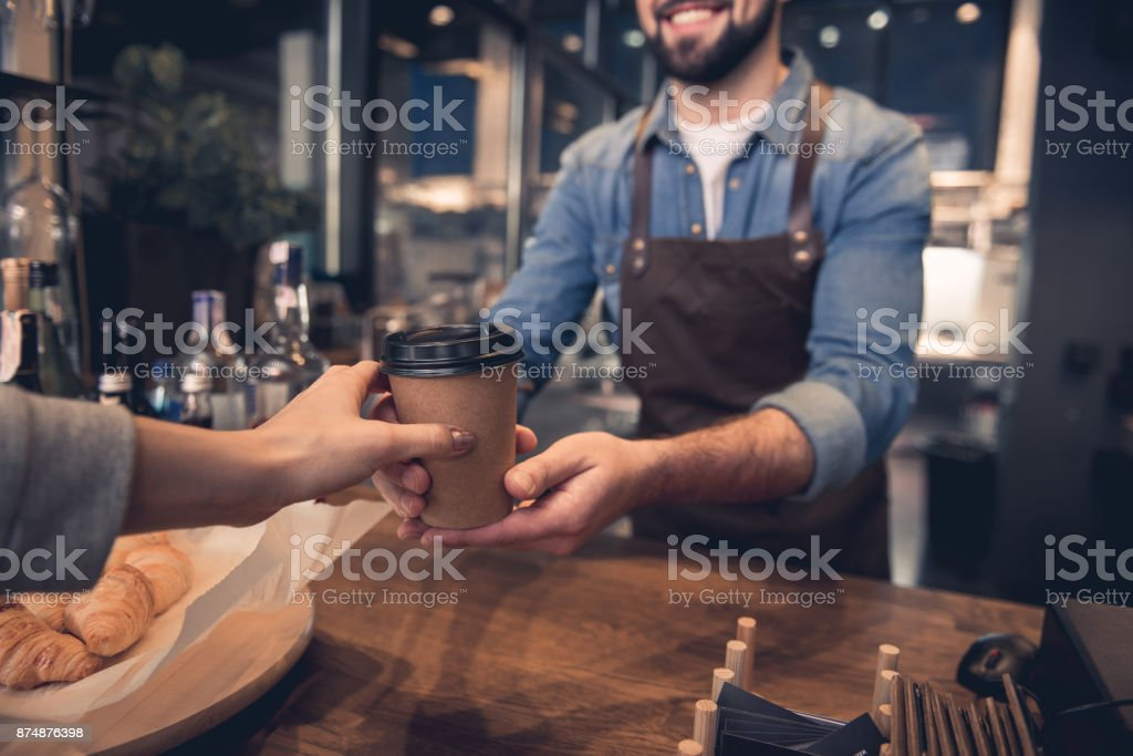 Worker giving mug of beverage to woman stock photo