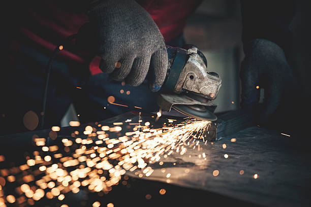 Worker grinding metal close up shot stock photo