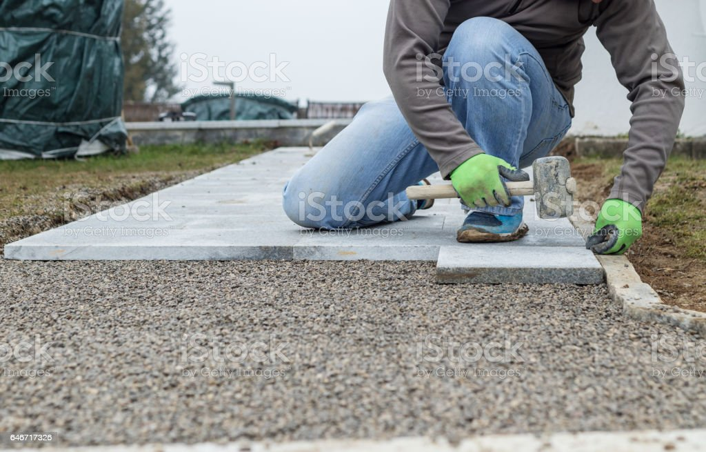 worker hammering the stone plates to install footpath at garden stock photo