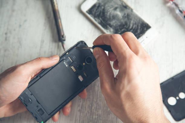 Arbeiter Hand gebrochen Telefon auf Holztisch – Foto