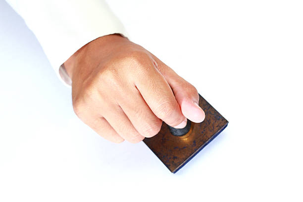 Worker hand holding rubber stamp Worker hand holdind rubber stamp isolate on white rubber stamp stock pictures, royalty-free photos & images