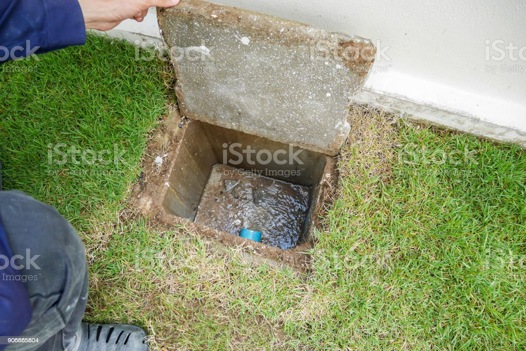 Worker hand open sewer of new house stock photo