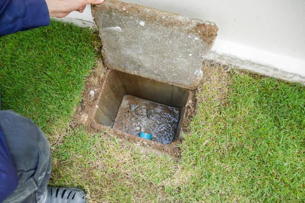 arbeiter hand öffnen kanalisation des neuen hauses - kanalisationsabflüsse stock-fotos und bilder