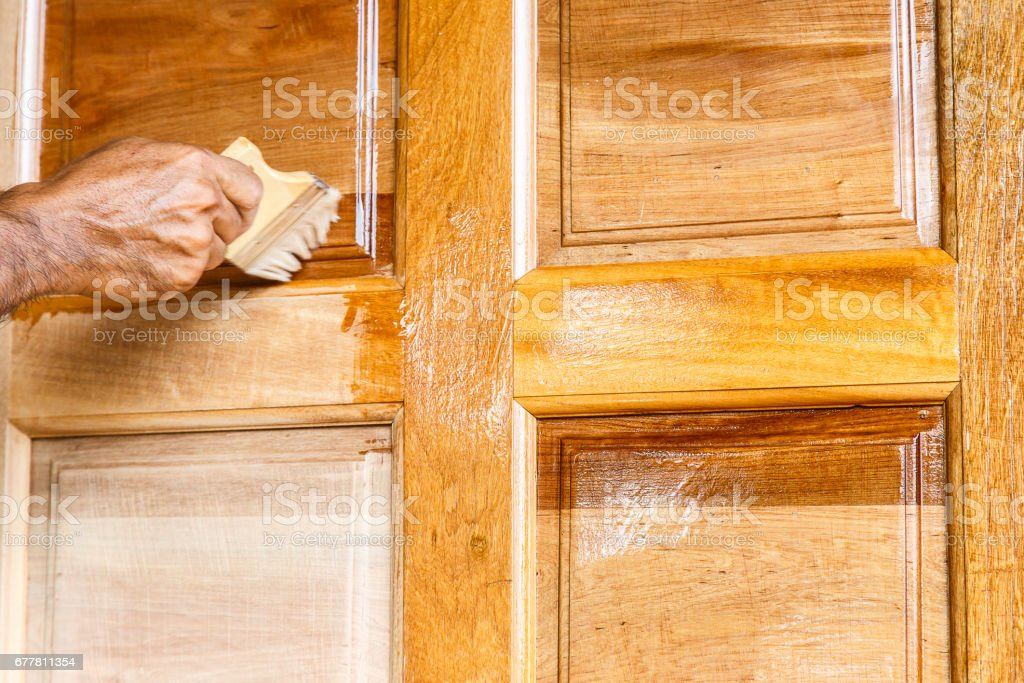 Worker hand painting wooden door with paintbrush, linseed oil varnish paint on wood stock photo