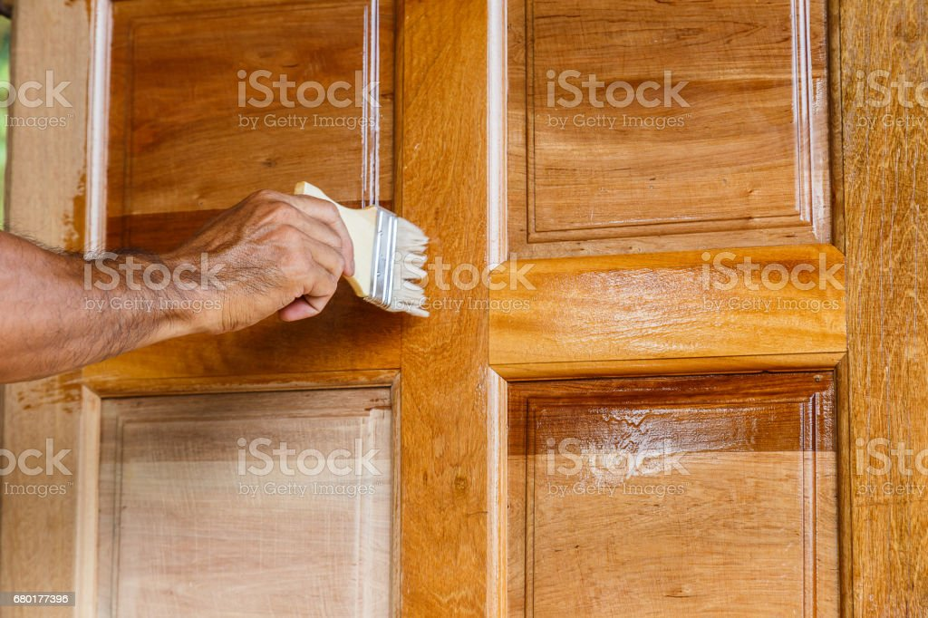 Worker Hand Painting Wooden Door With Paintbrush Linseed Oil Varnish ...