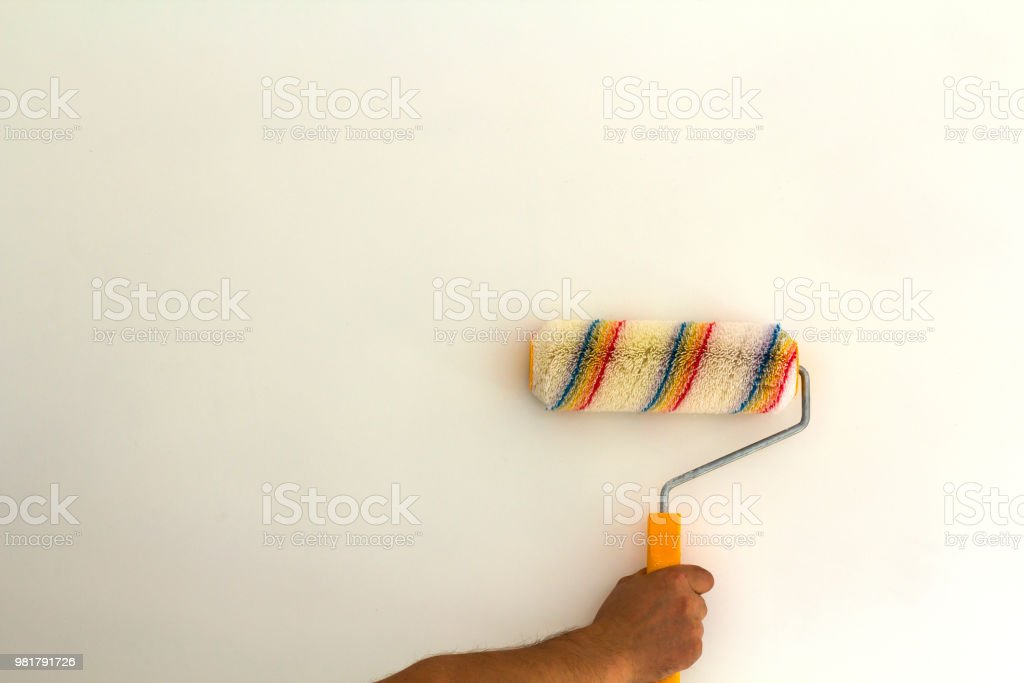 Worker Hand With Paint Roller Brush Near Wall In Renovated