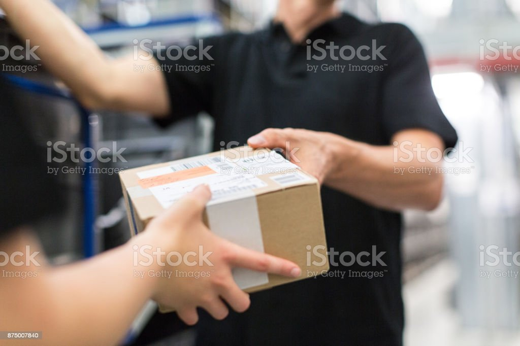 Worker handing over a package to colleague royalty-free stock photo