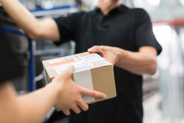 Worker handing over a package to colleague stock photo