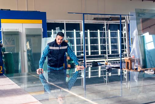 Worker handling glass sheet in warehouse