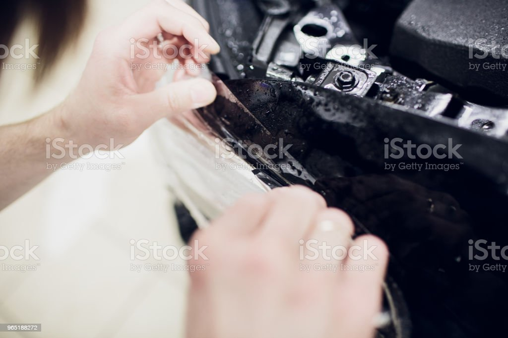 Worker hands installs car paint protection film wrap auto headlight royalty-free stock photo