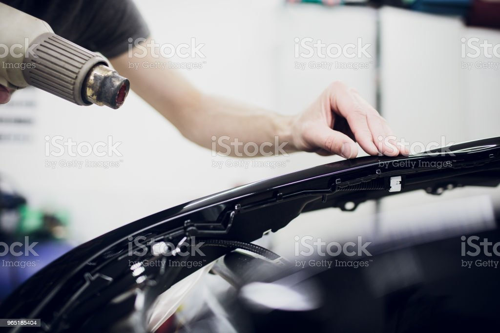 Worker hands installs car paint protection film wrap bumper zbiór zdjęć royalty-free