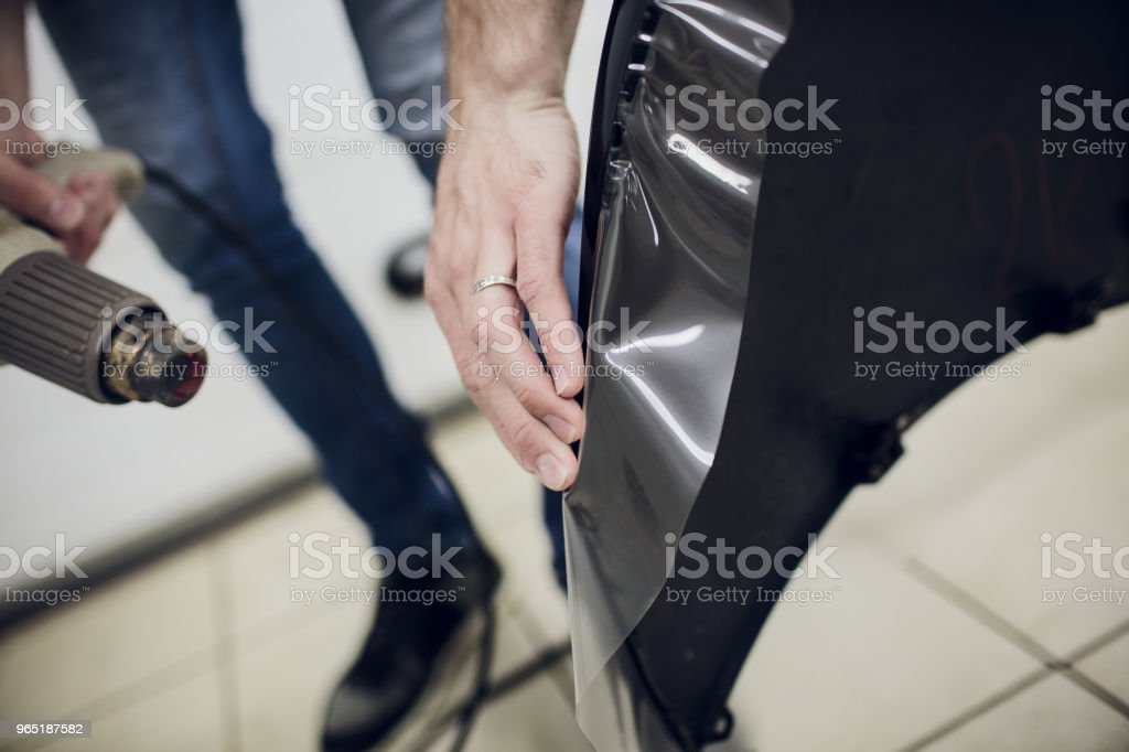 Worker hands installs car paint protection film wrap bumper royalty-free stock photo