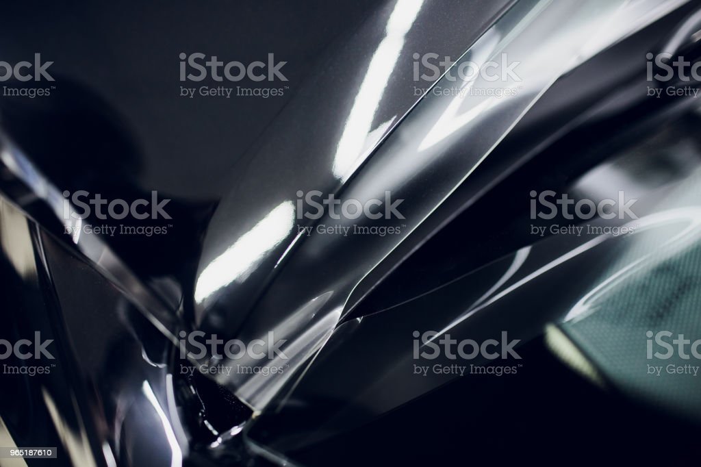 Worker hands installs car paint protection film wrap hood zbiór zdjęć royalty-free
