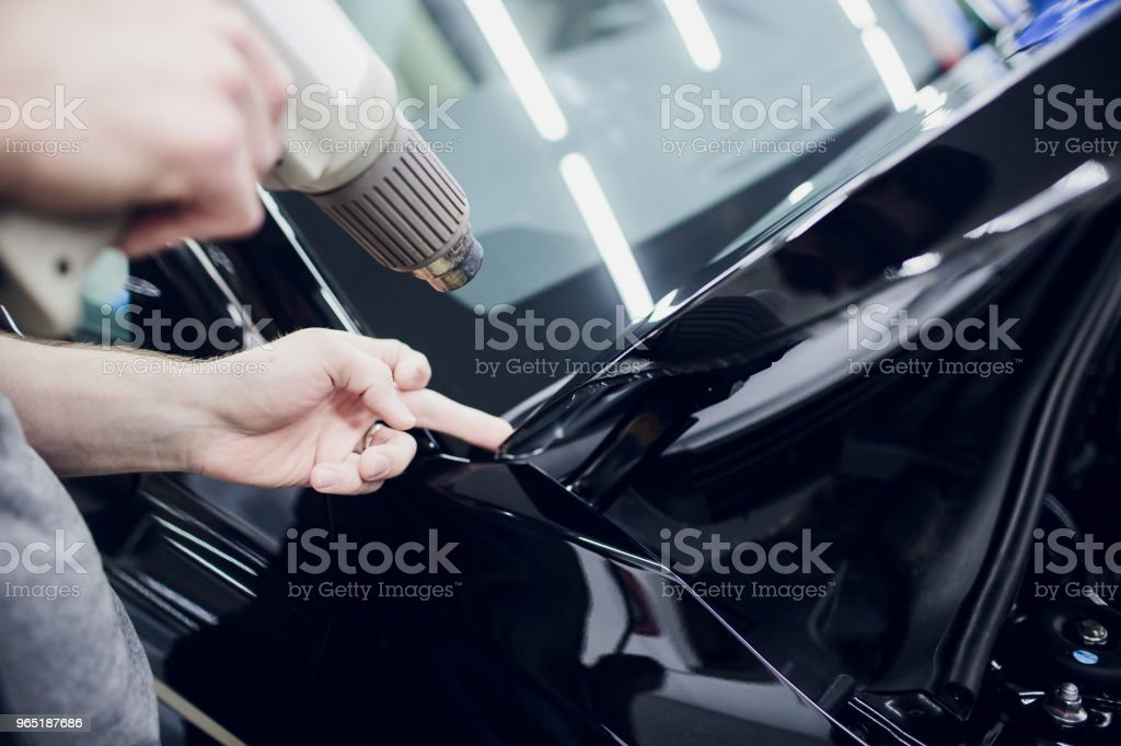 Worker hands installs car paint protection film wrap hood royalty-free stock photo