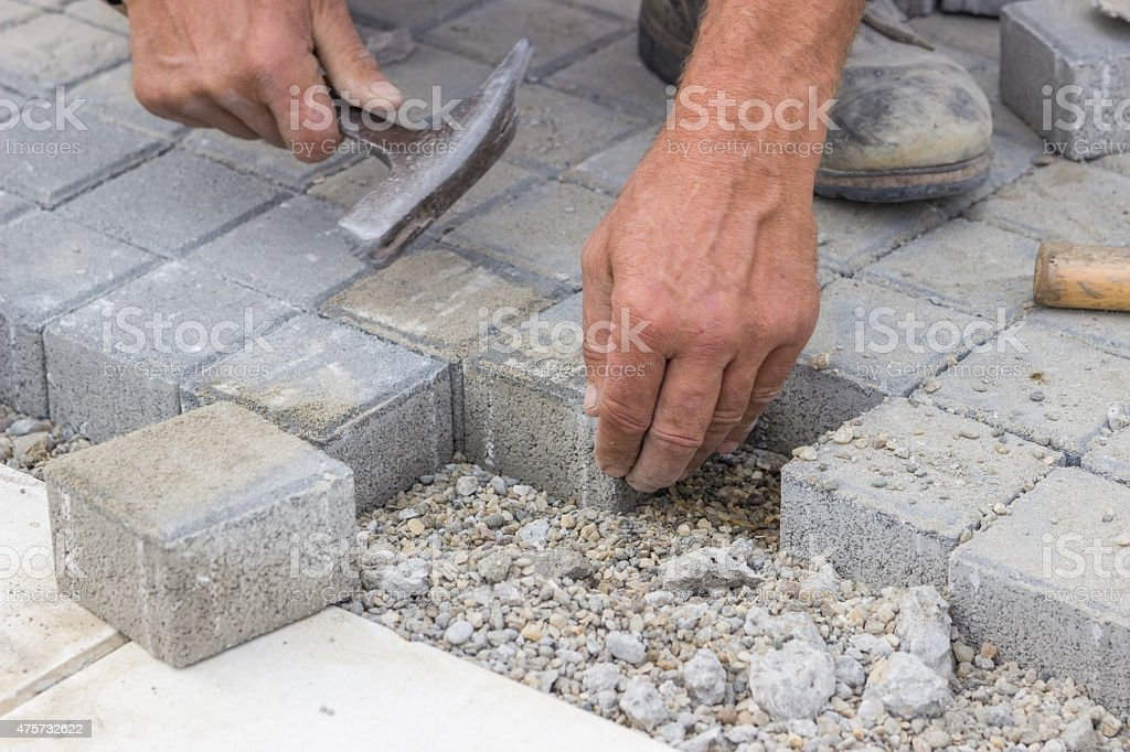 worker hands  laying concrete brick pavers 2 stock photo