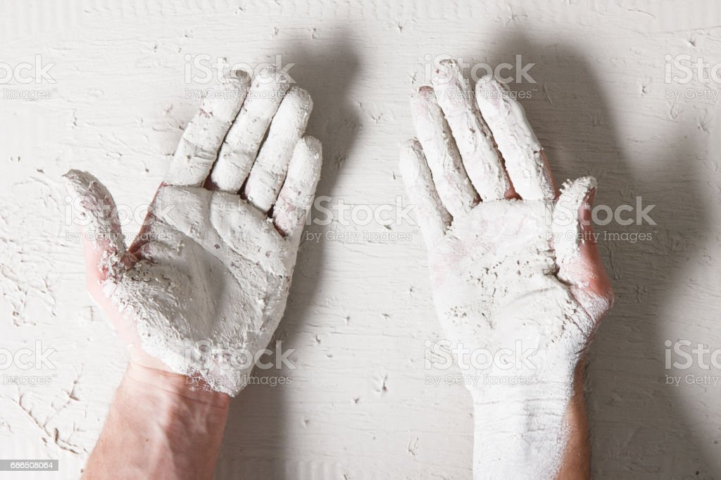 Worker hands on white plaster surface background foto stock royalty-free