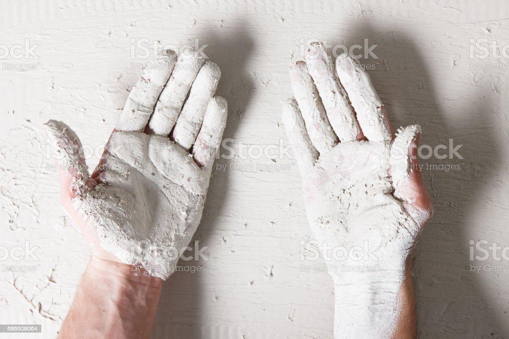 Worker hands on white plaster surface background zbiór zdjęć royalty-free