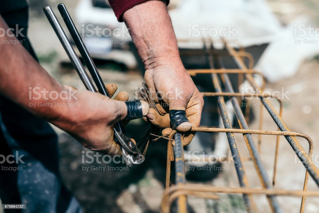 worker hands using steel wire and pincers to secure steel bars, preparing for concrete pouring on industrial construction site stock photo