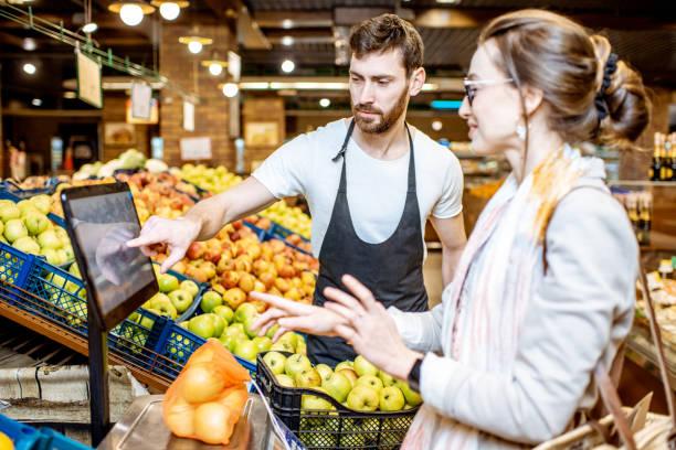 Arbeiter helfen Frau, Früchte im Supermarkt zu wiegen – Foto