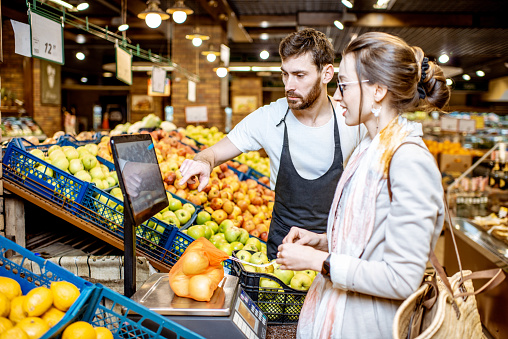 istock Worker helping woman to weigh fruits in the supermarket 1139293139